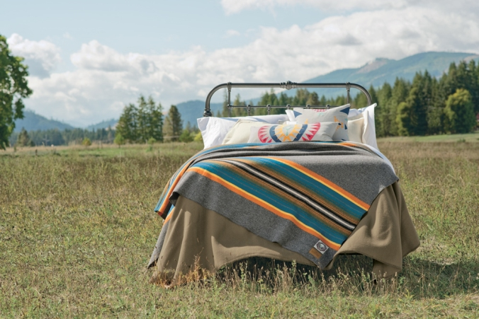 A bed made up with the Olympic national Park blanket by Pendleton sits in a mountain meadow.