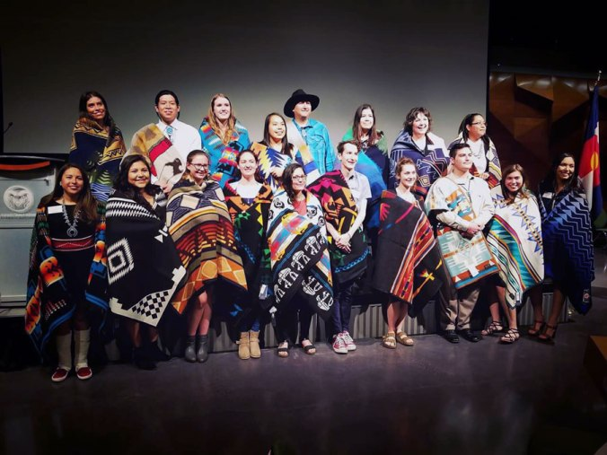 A proud group of Native American scholars are photographed in their Pendleton blankets.