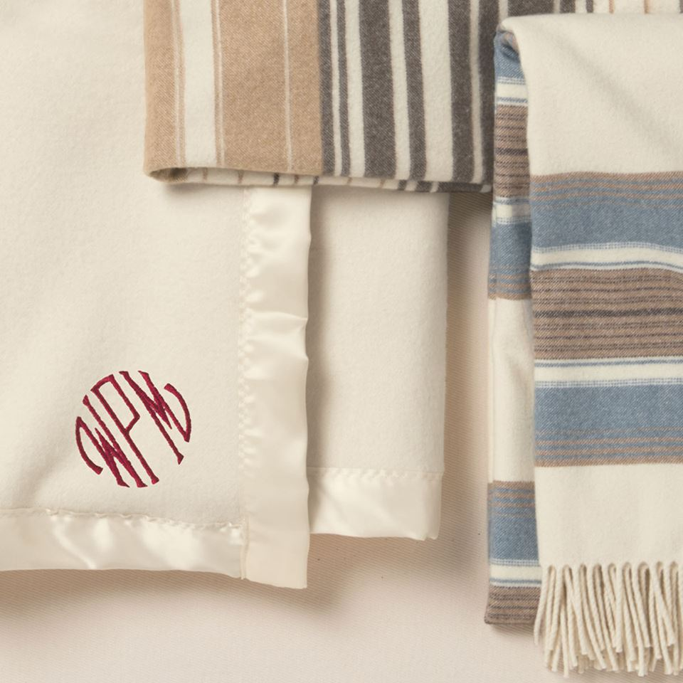 A monogrammed Pendleton bed blanket and two striped throws.