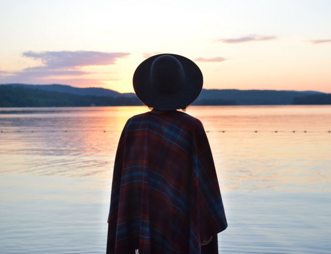A woman stands by the sore of the lake at sunrise, wrapped in a plaid Pendleton throw.