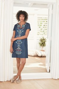 A woman stands in a doorway, wearing an embroidered shift dress.