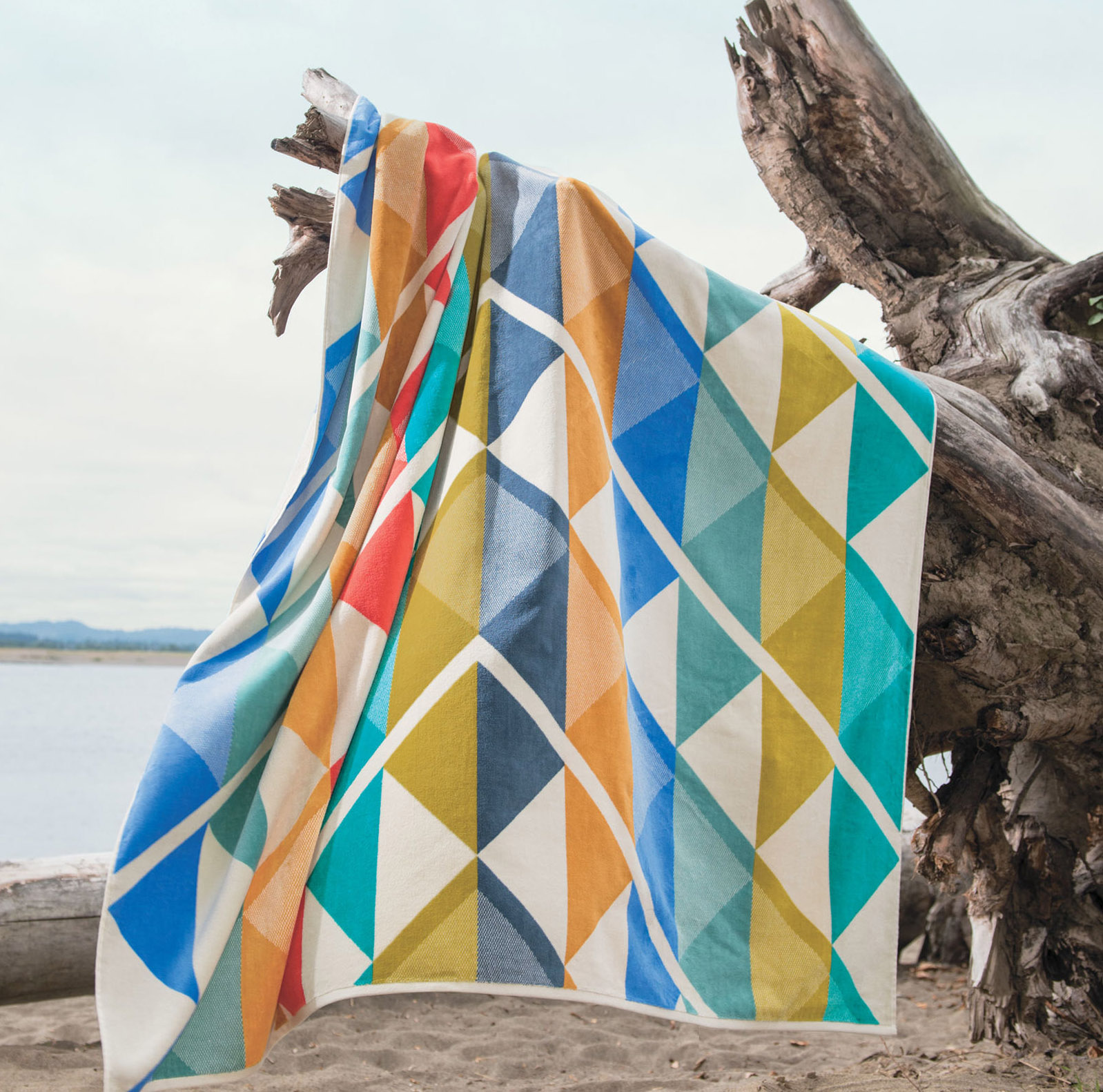 A Pendleton geometric spa towel hangs on a piece of driftwood on the seashore.