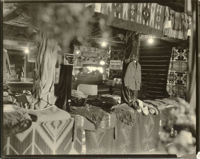 Circa 1911 –A cozy counter display of Pendleton blankets, steamer rugs (fringed throws), wool socks and men's hunting jacket.