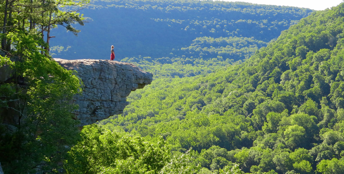 A woman stands on a rocky outcropping, taking in a view of the Ozark Mountains. Photo by Greg Hatten