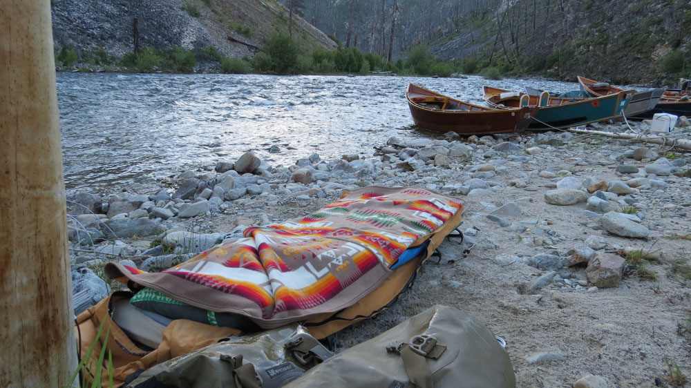 Greg Hatten makes camp on the banks of the Middle FOrk of the Salmon RIver, with his cot, Pendleton blanket, and boats in the distance.n Photo by Greg Hatten