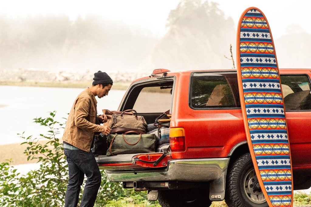 A man unpacks the back of his rig, and a Ginew surfboard with a Pendleton pattern leans against the vehicle.