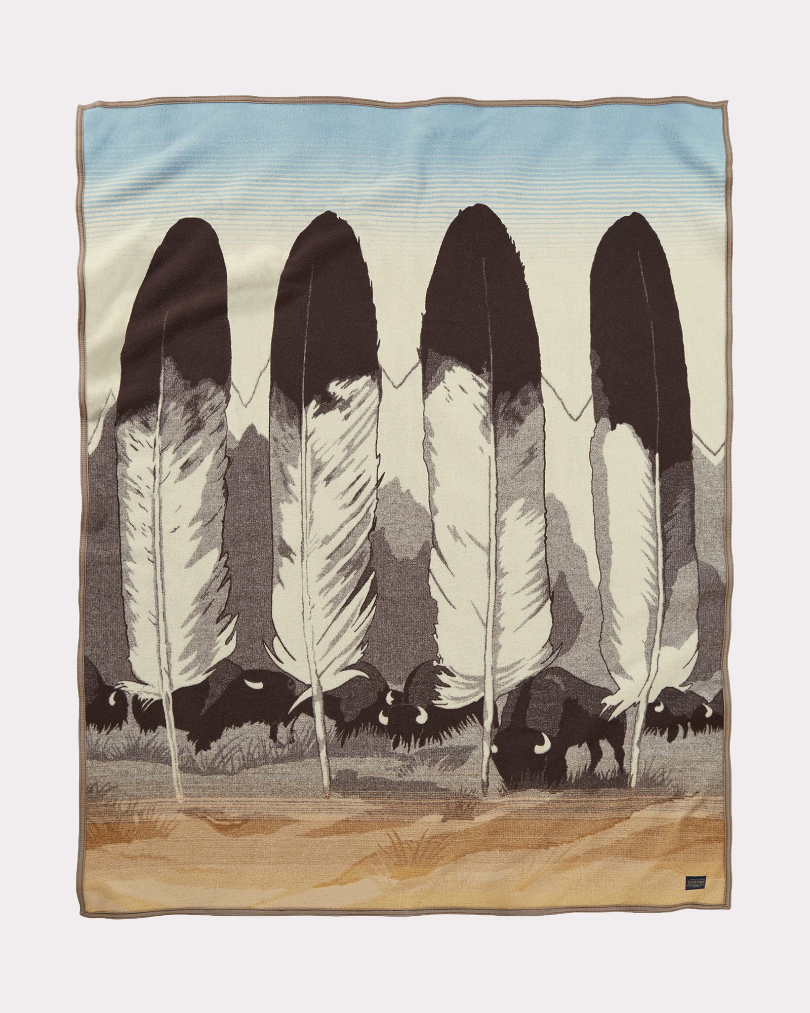 "Pendleton Legendary Series blanket, ""In Their Element"" designed by artist Joe Toledo. The blanket design contains four eagle feather, a mountain range, and a herd of grazing buffalo."