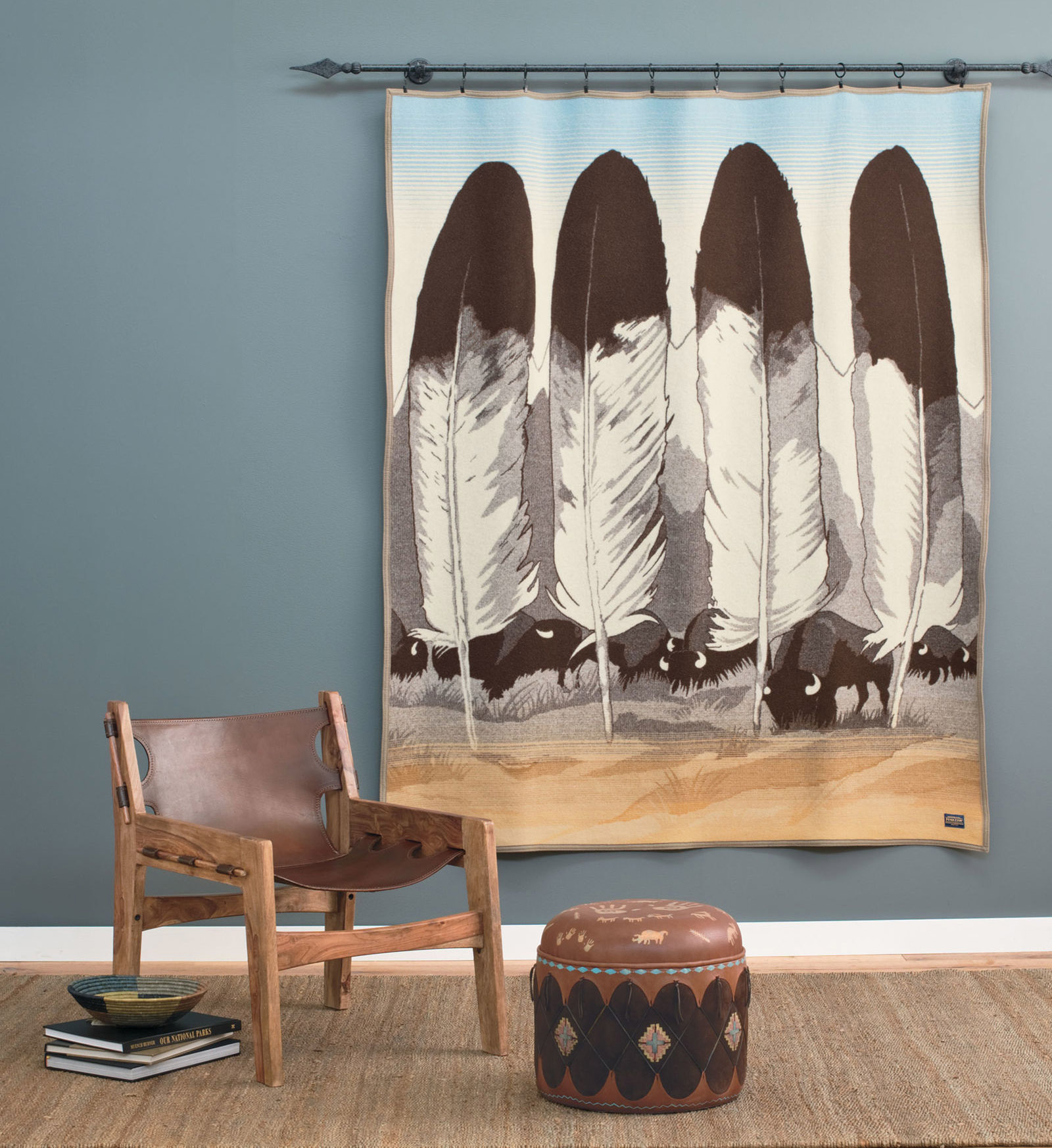 """On the wall hangs the Pendleton Legendary Series blanket, """"In Their Element"""" designed by artist Joe Toledo. The blanket design contains four eagle feather, a mountain range, and a herd of grazing buffalo."""