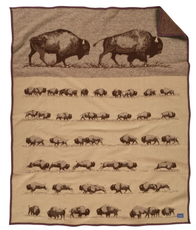 "The ""Buffalo Roam"" blanket by Pendleton Woolen Mills, from a work of art by Joe Toledo. At the top of the blanket, two large buffalo travel to the right. Below them, six rows of smaller buffalo are shown. Mr. Toledo's buffalo studies show the strength and agility of this massive animal."