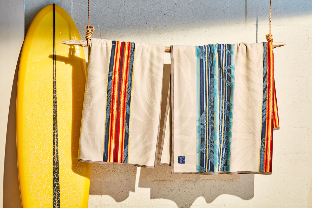 two Pendleton and Tommy Bahama collaborative serape blankets hang from a piece of driftwood next to a yellow surfboard.