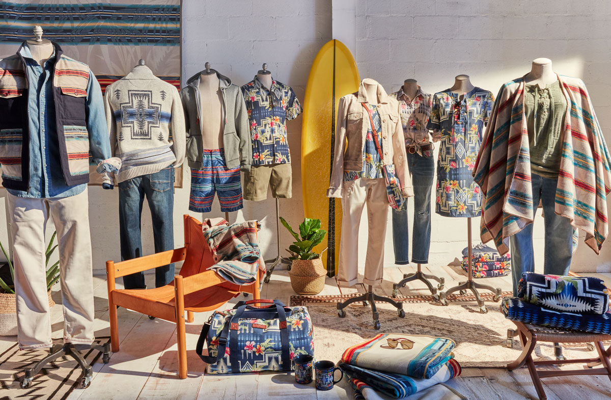 A photo of the goods included in the Pendleton collaboration with Tommy Bahama, including a vest, a sweater, a hoodie, a shirt, a bag, a poncho and a blanket. These goods are displayed on dressmaker forms in a sunny room.