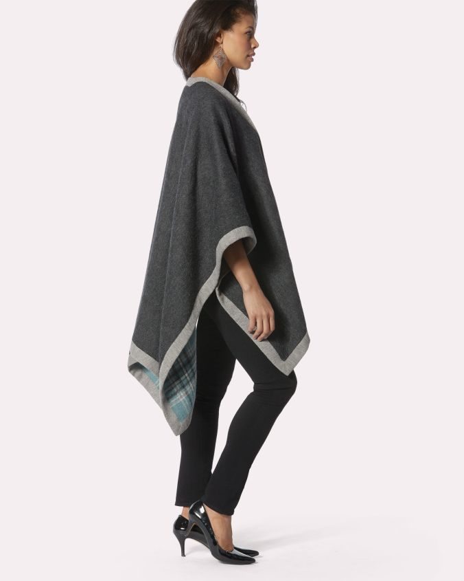 A model stands in profile, wearing a reversible cape of alpaca wool. One side is blue and grey plaid, the other is charcoal grey, with a light grey binding.