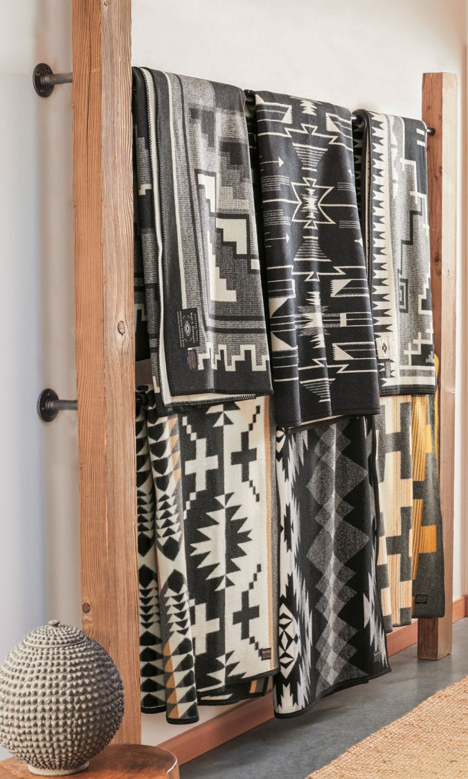 Six black and white Pendleton blankets, displayed on a wall mounted rack.
