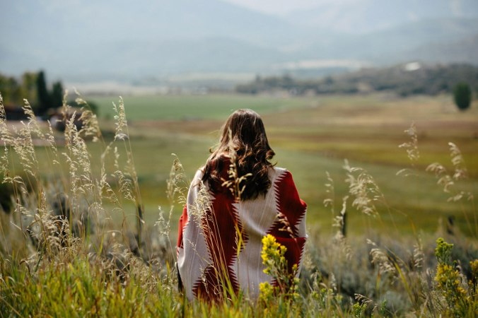 A woman sits, wrapped in a Pendleton Brave Star blanket, in a mountain meadow. Her back is to the camera.