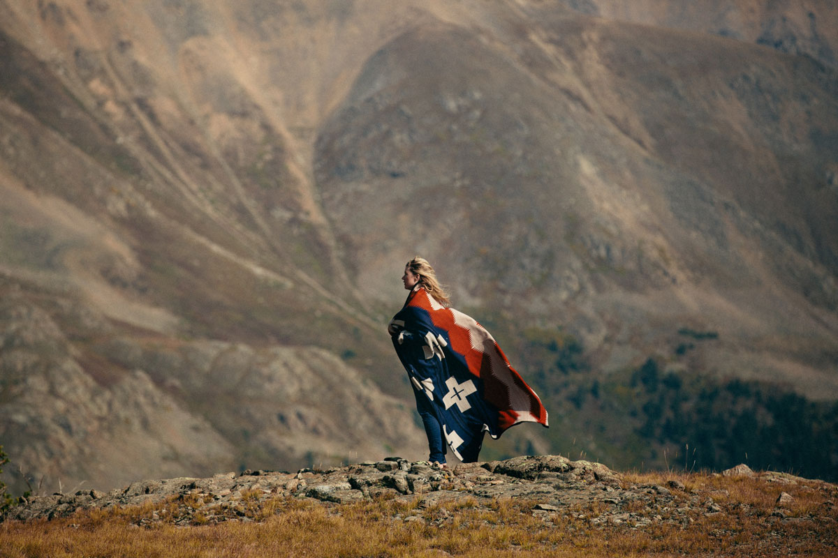 A young woman stands in front of a mountain, wrapped in a Pendleton Brave Star blanket. Her long blond hair and the blanket are blowing in the wind.
