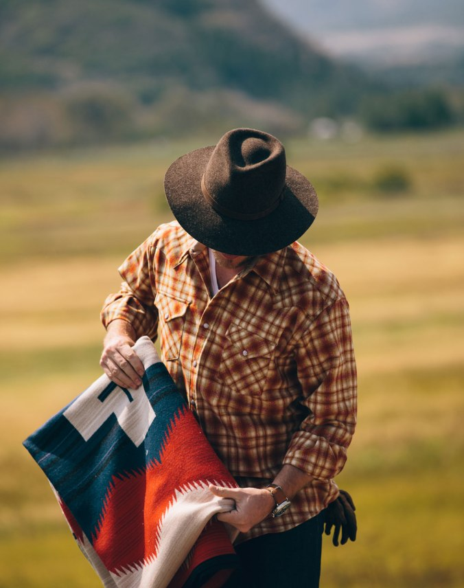 A man stands in a field before a mountain. He is wearing a plaid Pendleton shirt, and holding a folded Pendleton Brave Star blanket.