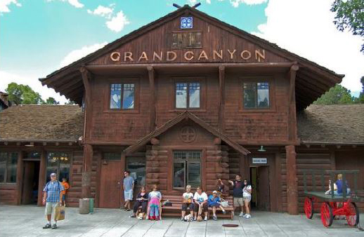 "A color photo of the exterior of the Grand Canyon Train Depot. A historic log building with the words ""Grand Canyon"" on the front gable."