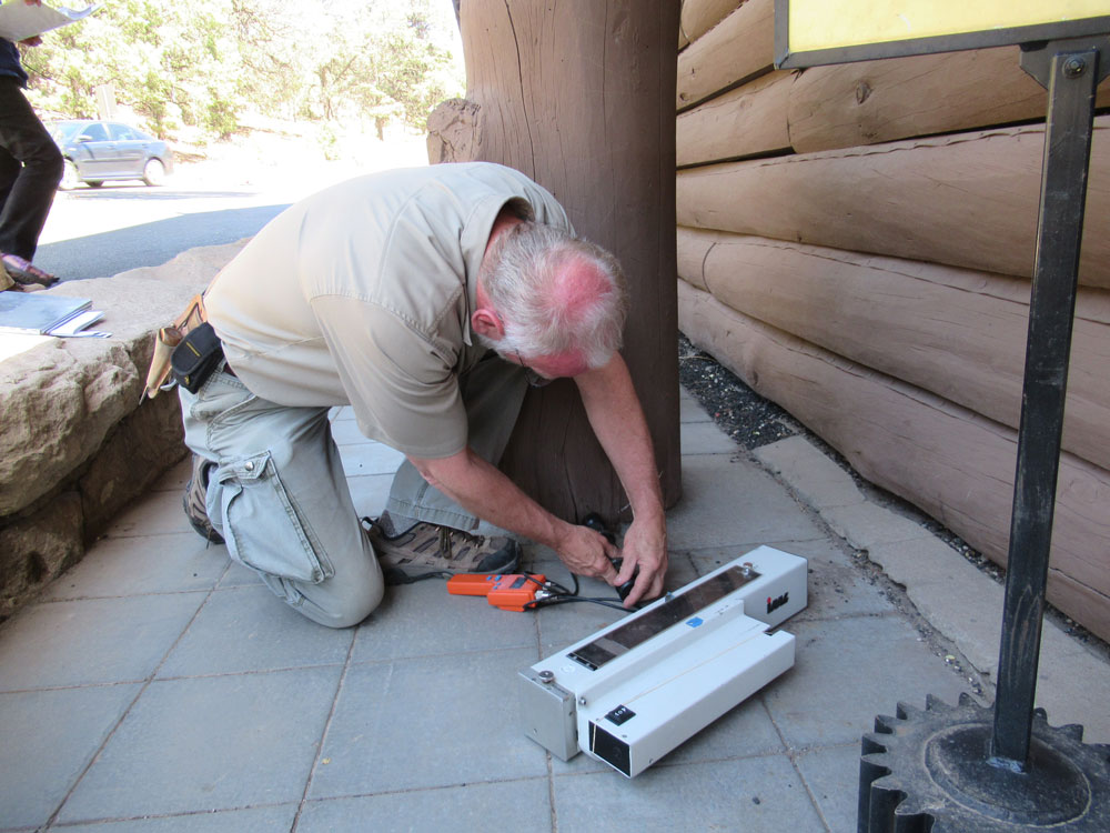 A man works on the exterior of the Grand Canyon Depot building.