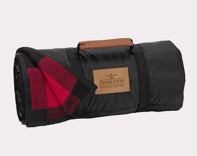 A Pendleton roll-up blanket in a black and red plaid with a black nylon backing and built-in handle with brown leather grip.