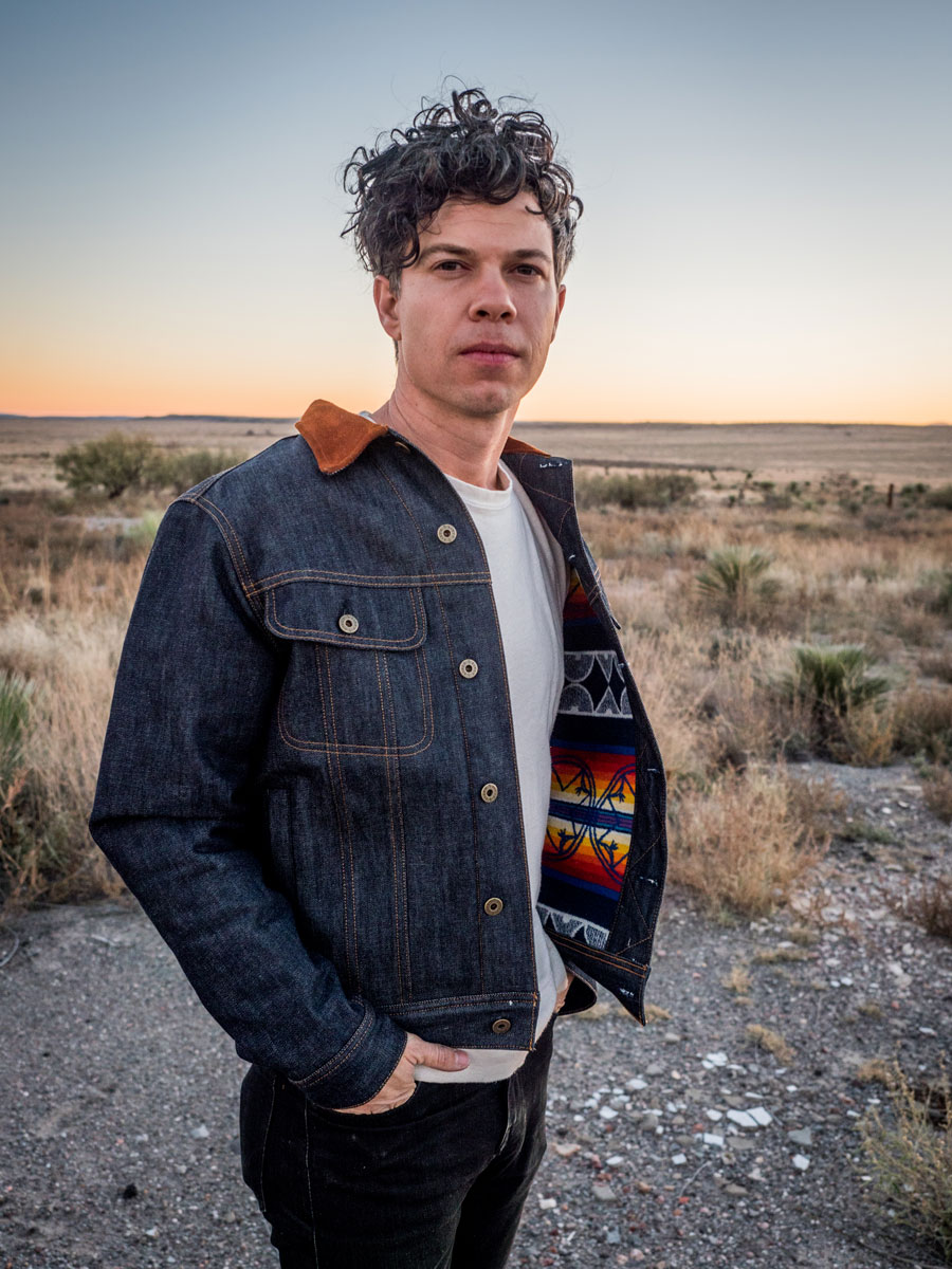 A man stands in a deserted field wearing a Ginew x Pendleton denim jacket.