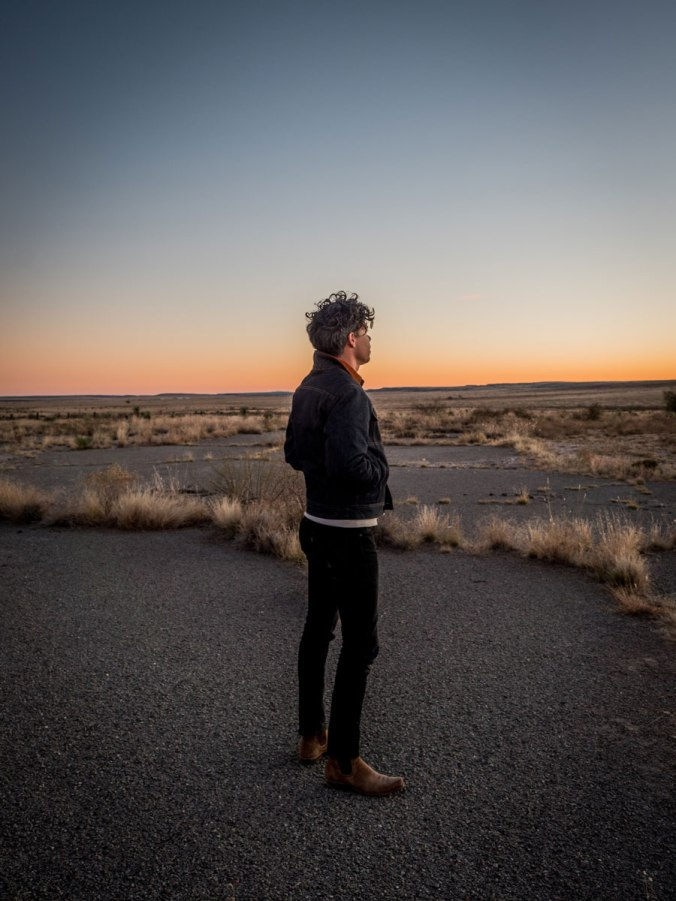 A man stands in the desert, the horizon glowing with either sunrise or sunset, wearing Ginew denim jeans and jacket.