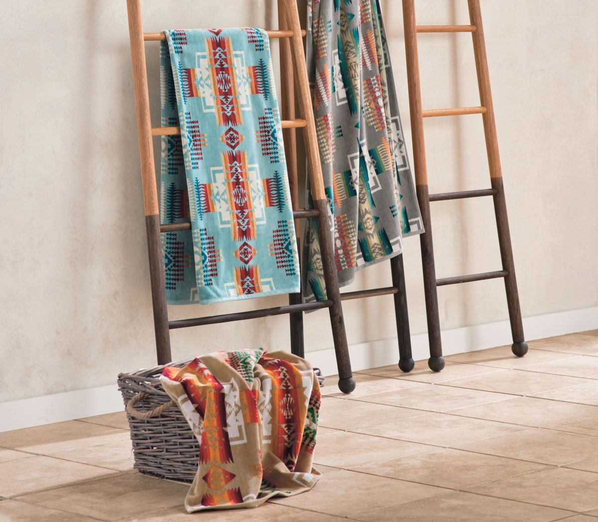 Colorful Pendleton beach and spa towels are draped on the rungs of three wooden ladders, and one is in a basket on the tile floor.