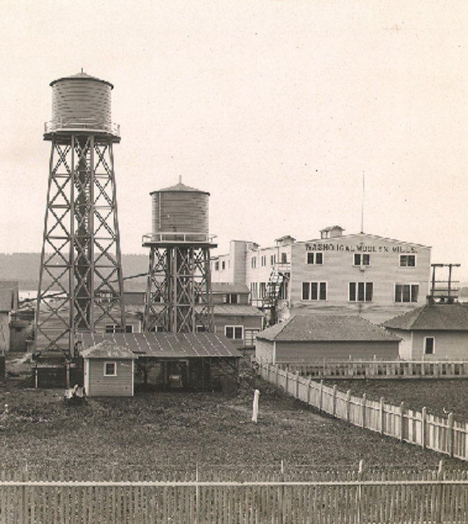 A vintage sepia-toned photo of the Washougal woolen mill owned by Pendleton Woolen Mills. The mill is two stories tall and in the photo, it is dwarfed by two water towers.