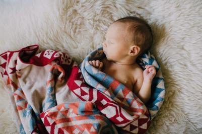 A newborn baby, wrapped in a knitte pendleton baby blanket, lies on a soft white sheepskin.
