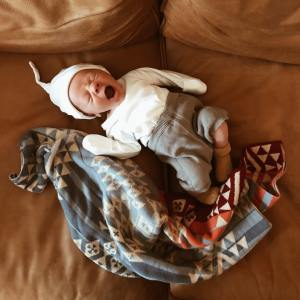 A newborn baby lies on a leather sofa next to a knitted pendleton baby blanket. The baby is wearing soft knitted clothing and a stocking cap, and the baby is yawning.