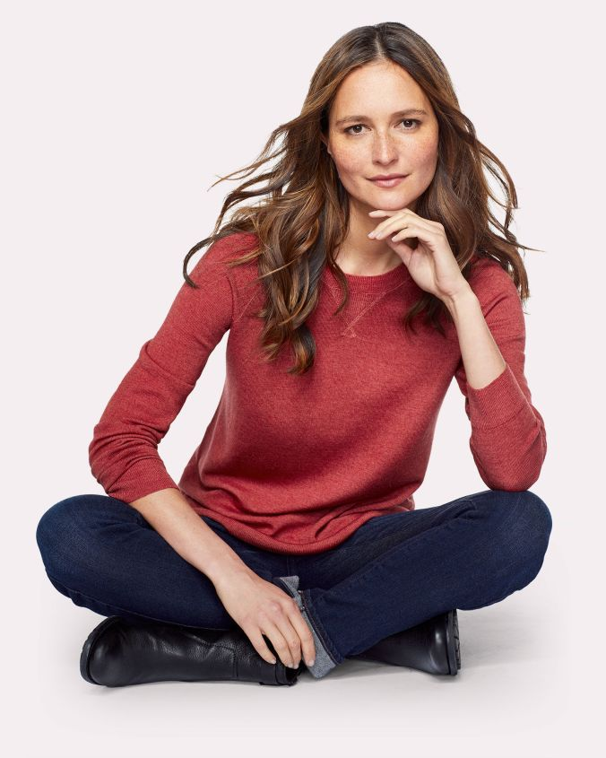 A brunette woman sits crosslegged on the ground. She is wearing a dark red sweater, jeans, and black boots.
