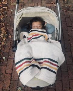 A toddler with adorable curly dark brown hair is asleep in a stroller, covered by a knitted Pendleton Glacier Park stroller blanket.