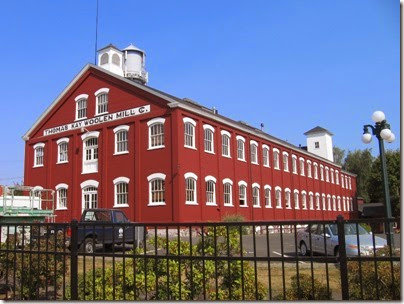 A photo of the Thomas Kay Woolen Mill in Salem, Orebon. This 2.5 story building is red brick with rows of white-trimmed windows.