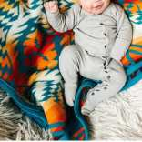 A smiling baby lies on a Pendleton Thunder and Lightning blanket. The baby is wearing a light grey thermal knit onesie with small wooden buttons.