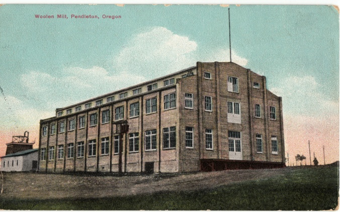 This photo is a vintage postcard image of the Pendleton, Oregon woolen mill. The building is grey brick, with rows of windows trimmed in white, and large front doors on the first, second and third floors at the front of the building.