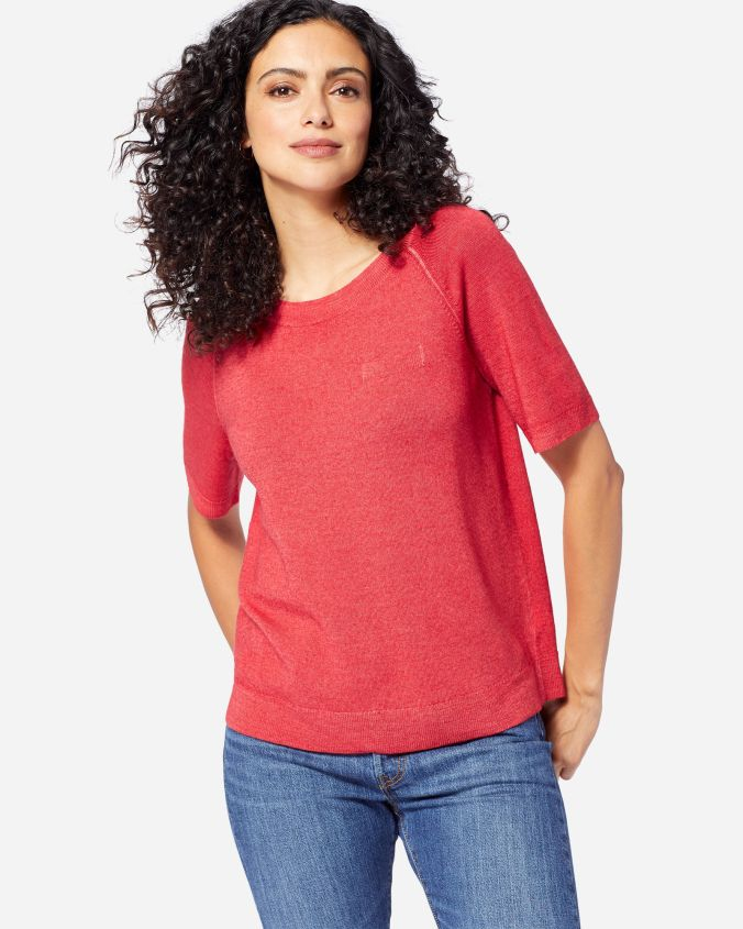 A woman with bountiful brunette curls stands with hands hooked in the back of her jeans pockets. She is wearing a brighter red sweater with short sleeves.