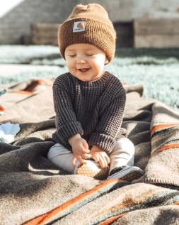 A smiling baby wearing a knit sweater, cap, track pants and small baby tennis shoes sits on a Pendleton camp blanket in the sunshine.