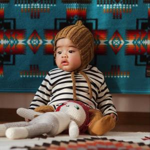 A sweet, chubby baby sits on a rug, leaning against a Pendleton baby blanket which is on a wall. The baby wears a kitted hat that ties under his chin, a striped shirt, and long knitted socks. A crocheted doll is on his lap.
