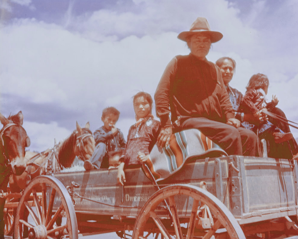 Archival photo from early 1900s of a Navajo family (father, mother, three young children) riding in a wagon with a Pendleton serape stripe blanket