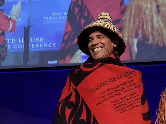 President Barack Obama is wrapped in a custom tribal robe, woven for the Swinomish Tribe, at the Tribal Nations Conference in Washington, D.C., 2016.