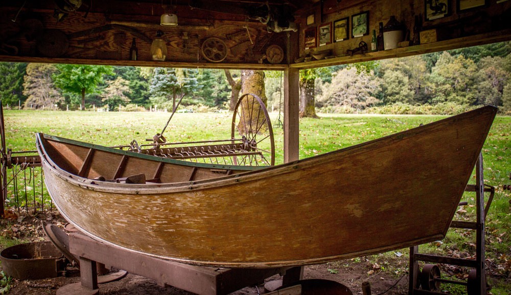 A wooden drift boat, part of a historical display, up on blocks in a shelter.