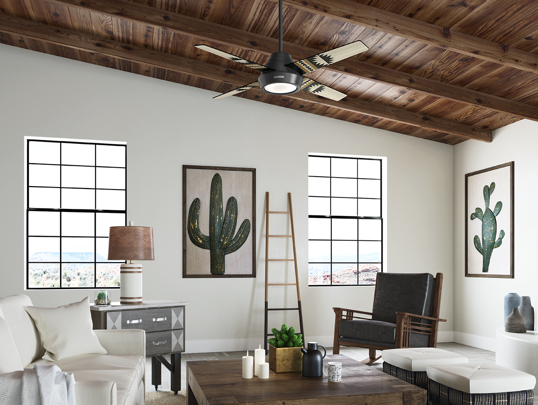 A living room featuring the Pendleton x Hunter fan. the room has white walls and a vaulted ceiling that's covered in wood, and paintings of cacti on the walls.
