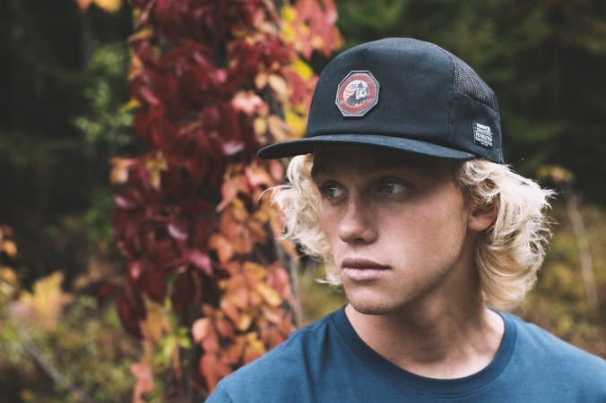 A young man stands in front of an ivy-covered tree, wearing a Pendleton x Hurley baseball cap.