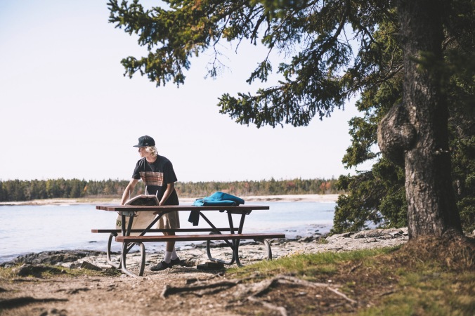 A young man leans on a wooden picnic table by the shore of a lake, wearing Pendleton x Hurley activewear.