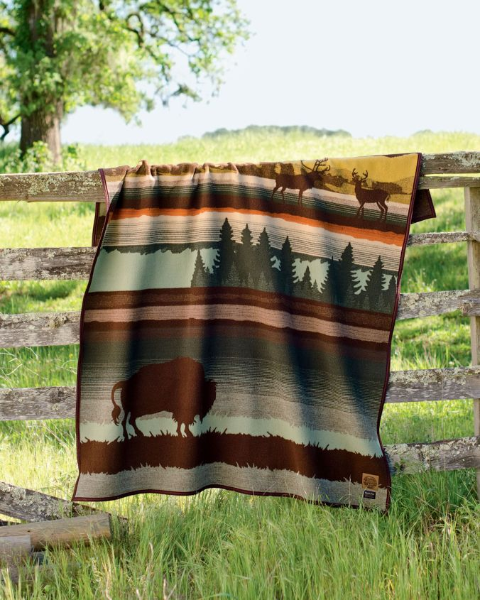 The Buffalo Wilderness blanket by Pendleton hangs over a wooden fence beside a pasture full of bright green grass.