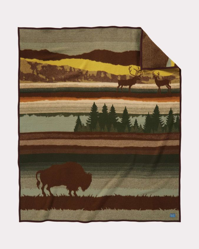 The Buffalo Wilderness blanket by Pendleton shows a buffalo (or bison) in silhouette against a landscapr of green, brown and gold. At the top of the blanket, two elk are shown in silhouette.
