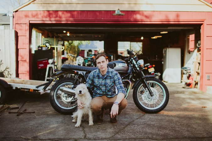 A man kneels in his driveway in front of a motorcycle, with is arm around a white fluffy dog. he is wearing a Pendleton Board Shirt in Original Surf Plaid.