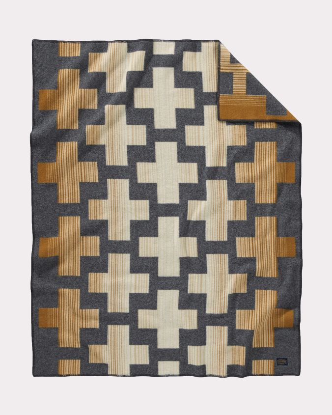 The Compass Point throw by pendleton is a geometric pattern of crosses in beige, cream and brown on a charcoal background.