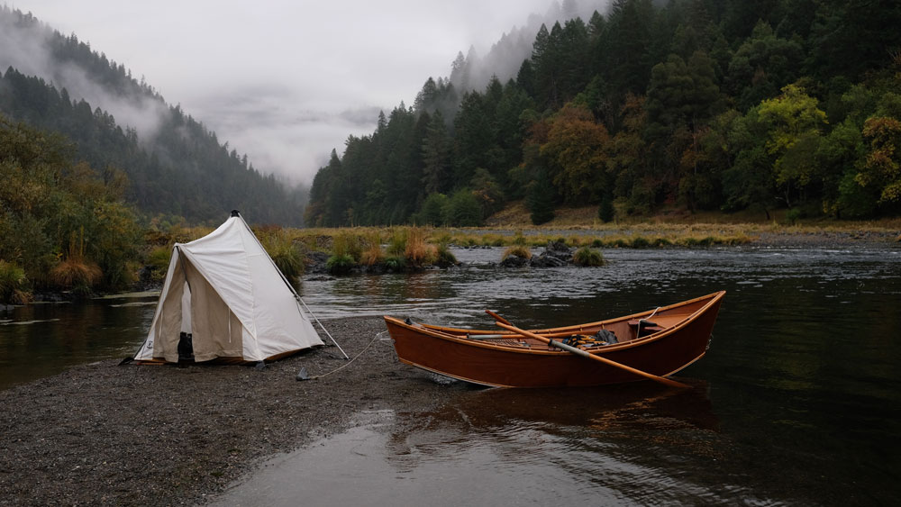 Morning on the river: a canvas tent and an empty wooden drift boat on a river at sunrise.