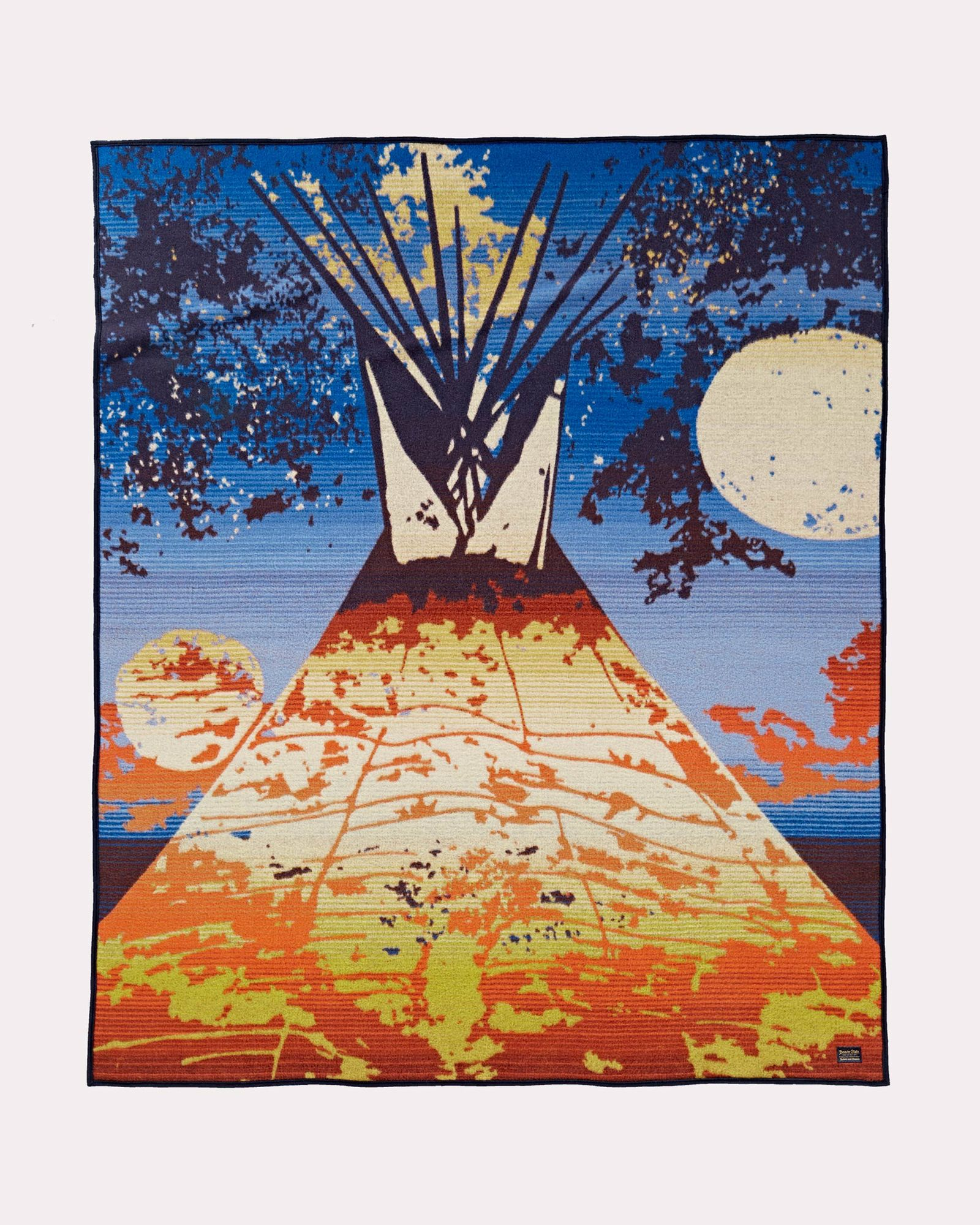 The Full Moon Lodge blanket by pendleton shows a bright orange and gold teepee against a dark blue sky, wit a full moon shining through tree branches. This blanket was designed by artist Starr Hardridge.