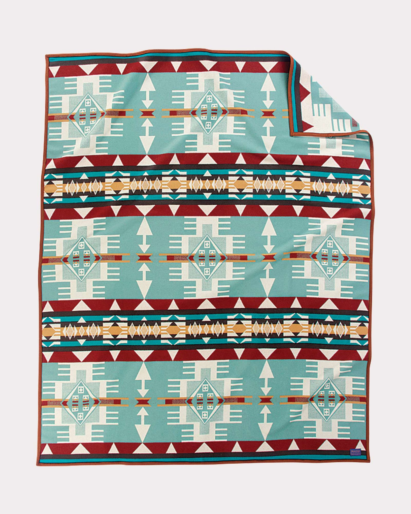The Hacienda blanket by Pendleton, a geometric pattern in turquoise, brown, gold and white.